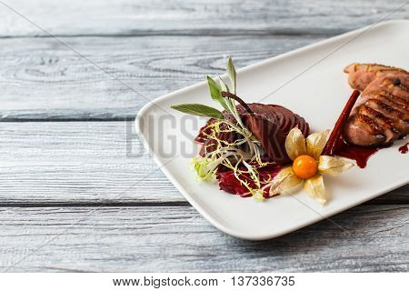 Cooked meat on white plate. Meat with herb and pear. Duck breast served at restaurant. Dish with wine sauce.