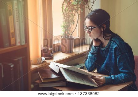Serious female hipster student reading book and sitting at the brown table in public university library. Young smart brunette young woman wearing glasses eyewear jeans blue shirt. Education school concept.