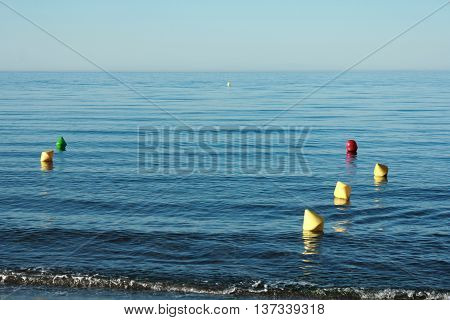 Bouys of different colors at the beach