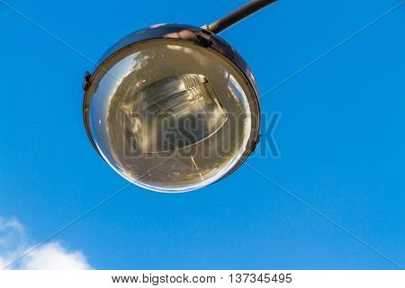 Near view of reflector and light bulb of street lamp against blue sky.