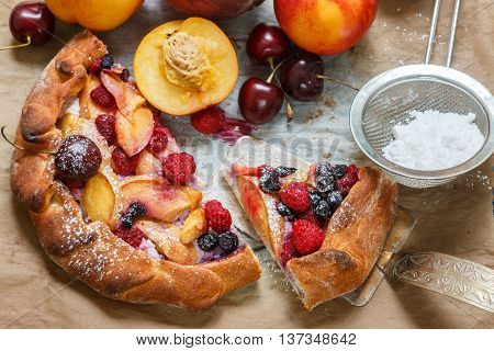 Outdoor homemade summer pie with cottage cheese fruit and berries - peach nectarine cherries blueberries raspberries. Galette. Selective focus