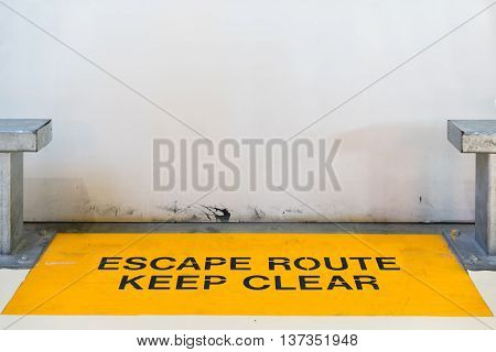 Escape route keep clear sign blocked by concrete wall with copy space clipping path for travel image adaptation