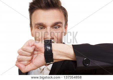 Time is money. Closeup portrait of businessman look at his watch disturbed, show that it is late, hurry up, check the time. Man in suit isolated at white background.
