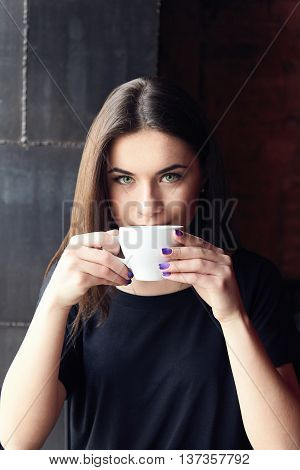 Beautiful girl drinking tea in cafe, holding cup both hands and thoughtfully looking at camera. Young woman enjoying her leisure time alone in coffee shop. Female with green eyes in black t-shirt.