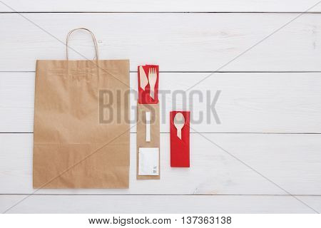 Copyspace at white wooden background for menu or recipe. Food delivery background, take away with brown paper bag. Fork and knife wrapped in paper, cutlery top view, flat lay