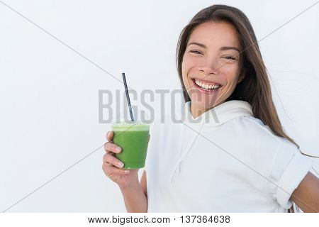 Happy Asian woman drinking healthy green spinach smoothie cup detox for weight loss diet. Young smiling fitness sporty girl with vegetable juice drink from juicing bar health trend, white background.