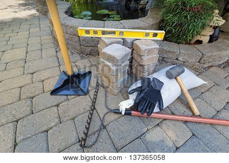 Stone Pavers for backyard patio pond hardscape with garden landscaping tools gloves level rubber mallet sand gravel tamper