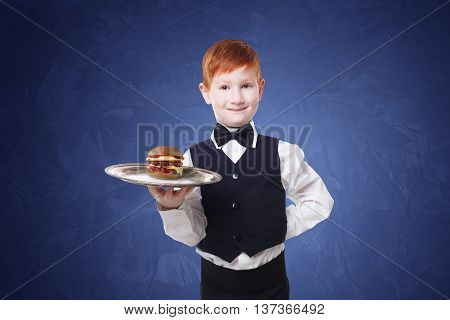 Little waiter stands with tray serving hamburger. Smiling redhead child boy in suit plays restaurant servant, gives burger at blue background