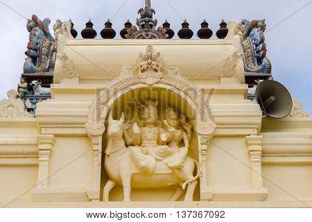 Tamil Nadu India - October 18 2013: Cream-colored statue of Lord Shiva and Parvati on their bull at Pillayarpatti Karpaga Vinayagar temple entrance.