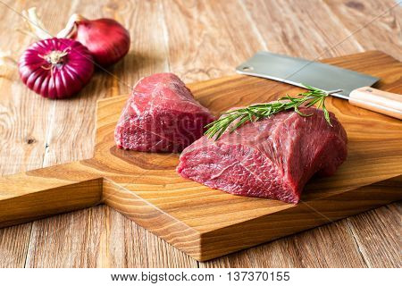 fresh meat on chopping board with rosemary, red onion. Raw meat. three peece of beef ready for cooking on wooden table . close up.