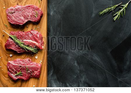 fresh meat on chopping board with rosemary, red onion. Raw meat. three peece of beef ready for cooking on wooden board on black background . close up. top view. place for text