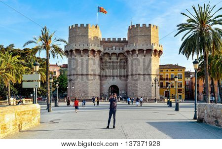 VALENCIA, SPAIN - JUNE 19: Some passerby and tourists in front of the Serranos Towers on June 19, 2016 in Valencia, Spain. Those towers, actually a gate, were part of the ancient city wall