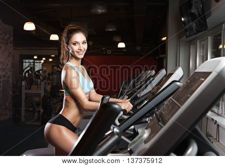 Beauty girl workout exercise on elliptic bike. Young, beautiful woman training by riding a bicycle in a gym. Concept of healtly lifestyle and sport.