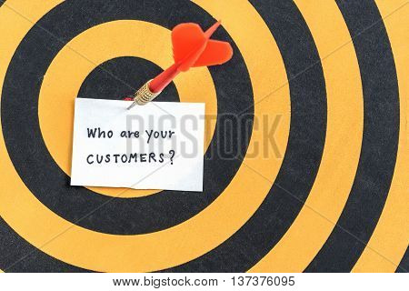 Target arrow hitting paper with alphabet letters of handwriting words who are your customers and question mark symbol over bullseye in dartboard Target customers marketing concept