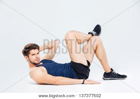 Serious young man athlete exercising and doing crunches over white background