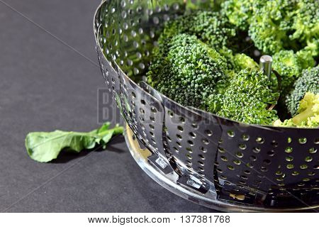 Fresh Brocolli florets in a steamer strainer with copy space on a moody background selective focus.