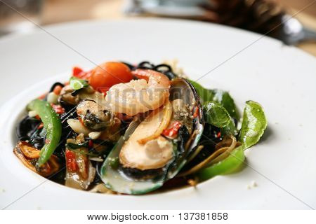 spaghetti with prawns and seafood on white plate, black spaghetti with seafood on table in restaurant, spicy spaghetti in food festival, italian food by spaghetti seafood, international food.