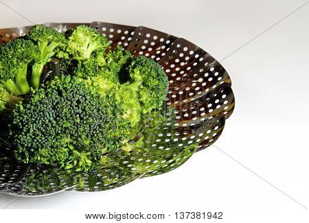 Fresh Brocolli florets in a steamer strainer with copy space on a white background selective focus.