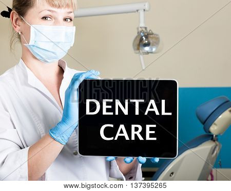 technology, internet and networking in medicine concept - femail dentist holding a tablet pc with dental care sign. at the dental equipment background.