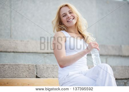 Cute girl sitting on bench with crossed legs, holding bottle of water and smiling