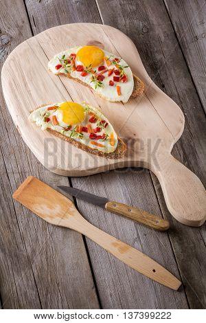 scrambled eggs with bread on cutting board closeup