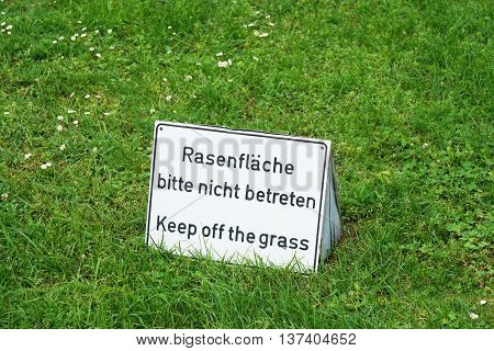 bilingual keep of the grass sign in German and English