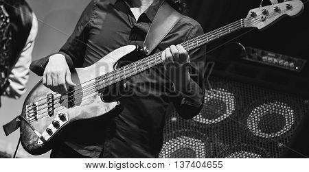 Rock music concert bass guitar player on a stage selective focus