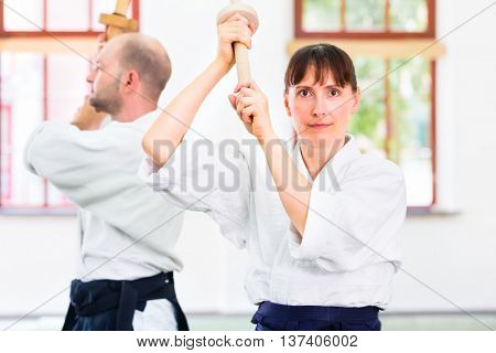 Man and woman fighting with wooden swords at Aikido training in martial arts school