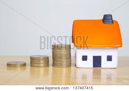 Money stacked in increasing piles next to a foam house