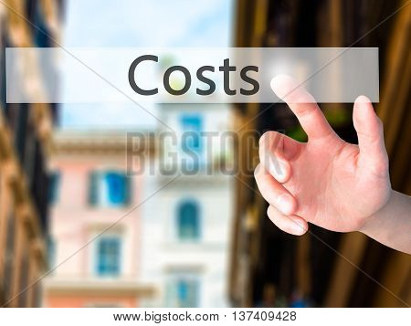 Costs - Hand Pressing A Button On Blurred Background Concept On Visual Screen.