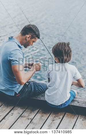Preparation before fishing. Rear view of father and son sitting at the quayside and preparing fishing rod for fishing