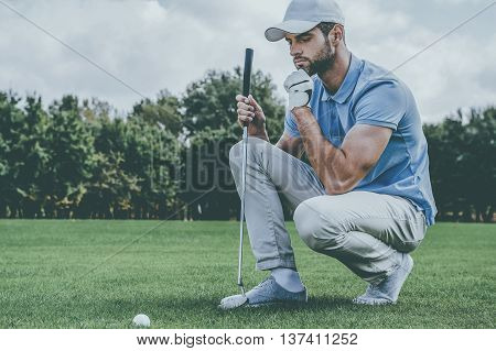 Thinking about the next shot. Cropped image of young golfer kneeling near the golf ball and holding hand on chin