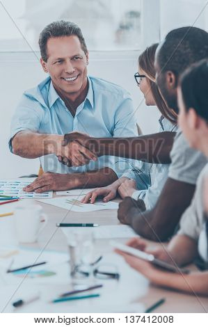 Welcome to team! Group of business people sitting in a row at the table while two men handshaking