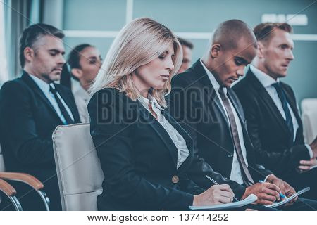 Business conference. Group of business people in formalwear sitting at the chairs in conference hall and writing something in their note pads
