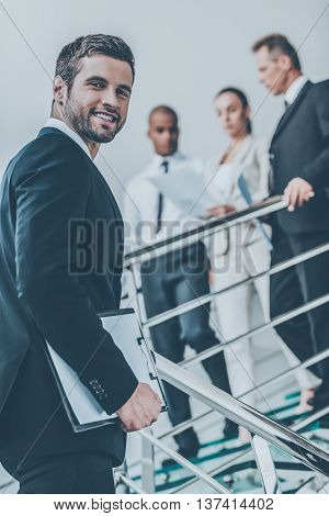 Confident businessman. Low angle view of confident young man in formalwear looking over shoulder and smiling while moving up by staircase with people in the background