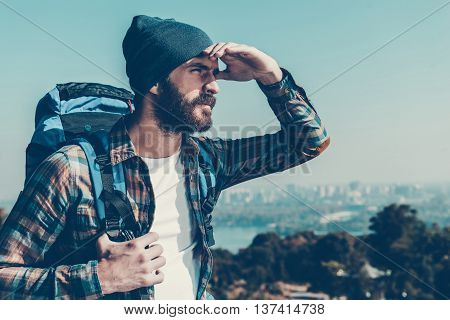 Looking at horizon. Handsome young man carrying backpack and looking away