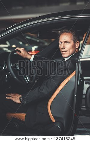 Car like business partner. Side view of confident senior man in formalwear sitting in car and smiling at camera