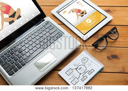 sport, responsive design and technology concept - close up of on laptop computer, tablet pc, notebook and eyeglasses with fitness application and scheme on wooden table