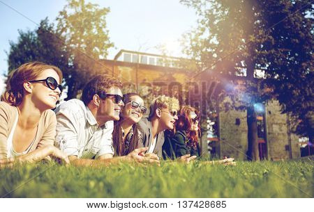 summer holidays, friendship, leisure and teenage concept - group of students or teenagers hanging out at campus or park
