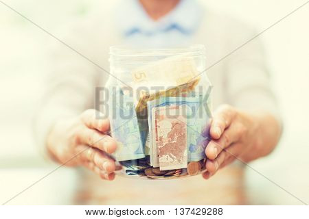 savings, money, annuity insurance, retirement and people concept - close up of senior woman hands holding money in glass jar