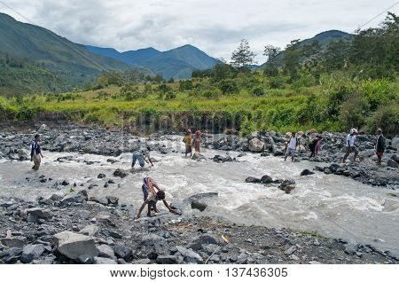 People Crossing River At Valley Of  River Baliem At Island New Guinea