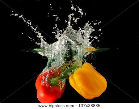A photo of a vegetables - peppers - dropped under water