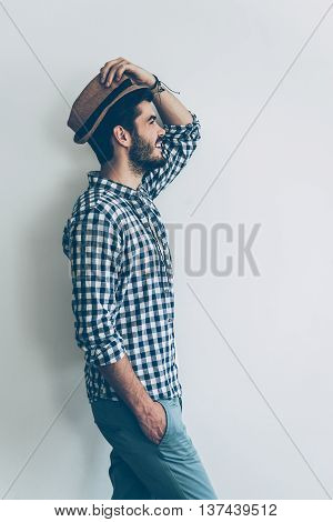 Stylish handsome. Side view of handsome young cheerful man holding one hand in pocket and adjusting his hat