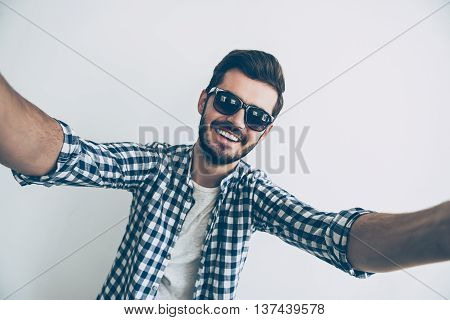Selfie time! Studio shot of handsome young man making selfie and smiling