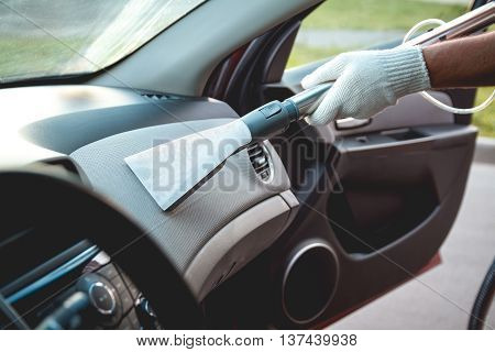 A man cleans the interior of the car. Vacuum cleaning the dashboard