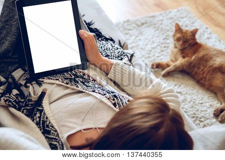 Woman in home cozy clothes lying on a sofa using tablet with headphones, looking at a lazy red cat sprawled on the carpet beside. Online education concept. e-learning. back view. Pet shop concept