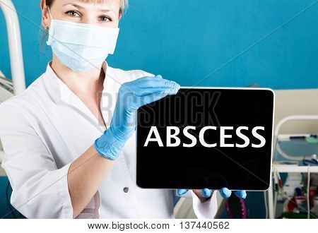 technology, internet and networking in medicine concept - femail dentist holding a tablet pc with abscess sign. at the dental equipment background.