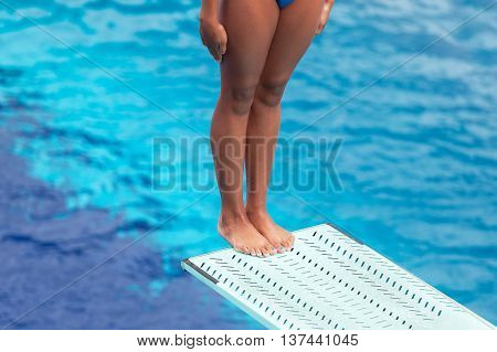 Girl standing on a springboard, preparing to dive into a swimming pool
