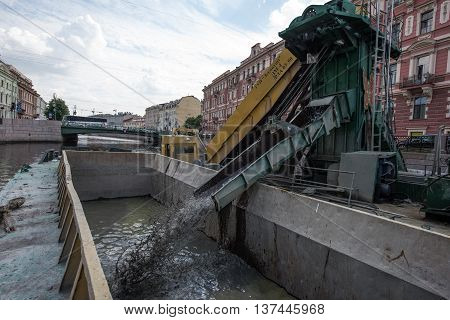 Saint-Petersburg Russia - June 30 2016: Cleaning the city canal bottom of the garbage in the city center with the help of a special installation on the boats.