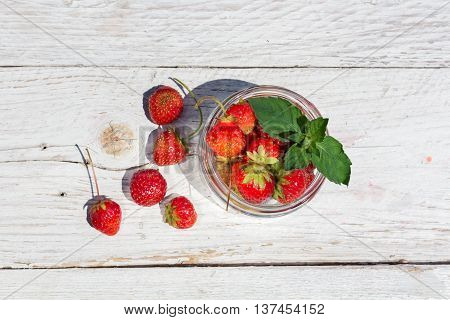 strawberries in a glass jar on old boards top view